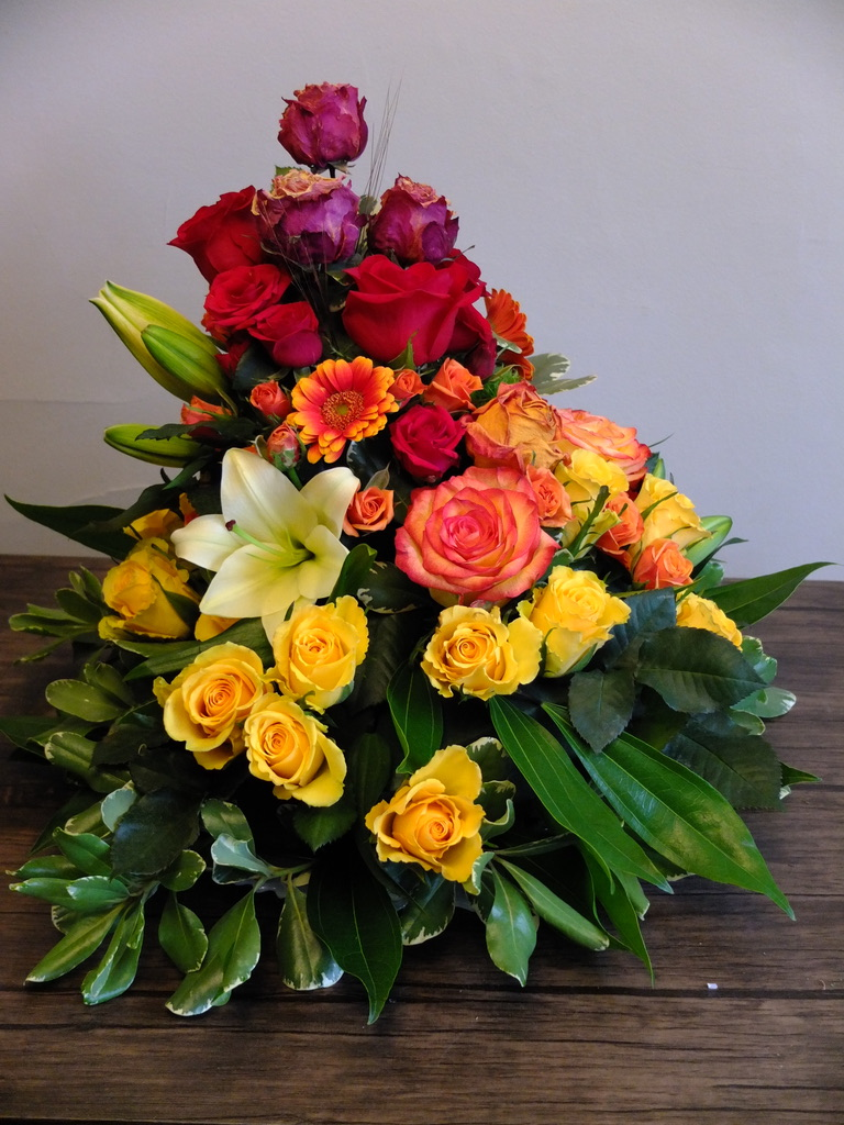Dried cherry brandy roses transition to red freedom roses which transition to bicoloured orange and red circus roses which transition to bright yellow brighton roses. Yellow lilies and the occassional mini gerbera dot the arangement as well as orange bicoloured spray roses. Pittosporum and laurel round out the base.
